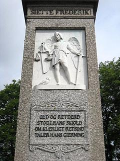 Monumentets forside med _Retfærdigheden_, og første strofe af Ingemanns digt.