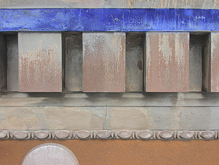 Hovedgesimsens pudsede del. Under cementmalingen ses den for Bornholmsk Cement så karakteristiske rosa farve.