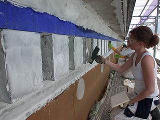 Borttagning af afsaltningspakning med gummispartel på vestfacadens hovedgesims.