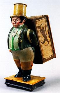 Mandlig figur med en kasse på ryggen. Indeni kassen findes en papirrulle med en tegning af et optog af deltagere i en Ponte Molle-fest til ære for Thorvaldsen