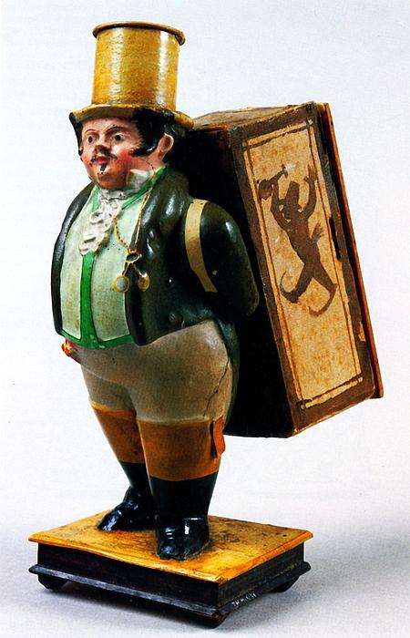 Mandlig figur med en kasse på ryggen. Indeni kassen en papirrulle, hvorpå kunstnerne er tegnet gående i et optog