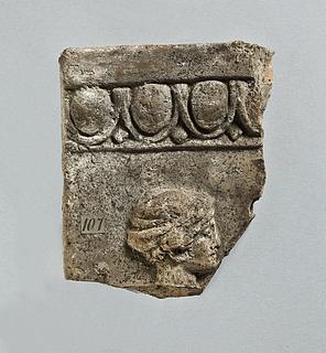 Campanarelief med kvindehoved med tætsiddende hue (kekryphalos). Romersk