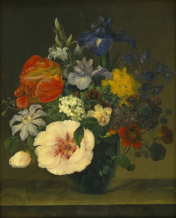 Et glas med blomster på en bordplade