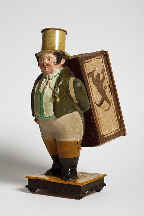 Mandlig figur med en kasse på ryggen. Indeni kassen en papirrulle hvorpå kunstnerne er tegnet gående i et optog
