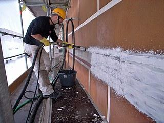 Påsprøjtning af afsaltningspakning på nordfacadens kordongesims for kemisk bortrensning af gipsbelægning.