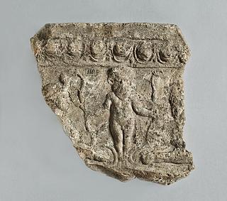 Campanarelief med lille skægget mandsfigur med krone (Bes) flankeret af to liggende sfinxer. Romersk